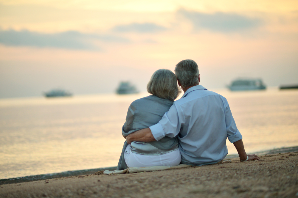 Happy Mature couple relaxing on beach at sunset,back view