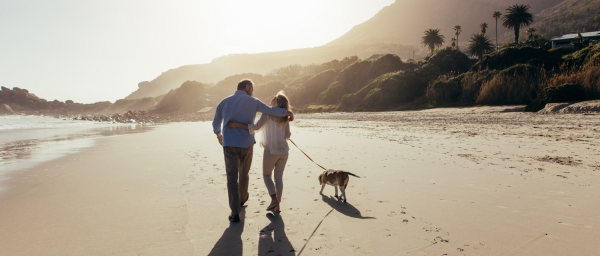 A couple strolling on the beach in retirement in Spain.